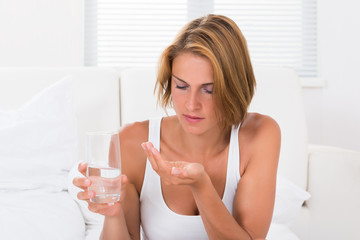 Woman Holding Medicine And Glass Of Water