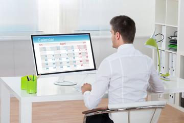 Fototapete - Businessman Looking At Calendar On Computer