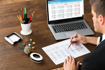 Fototapete - Businessman Marking Date On Calendar