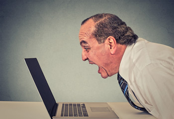 furious business man working on computer, screaming