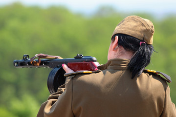 Girl in uniform and cap holding automatic rifle and aiming