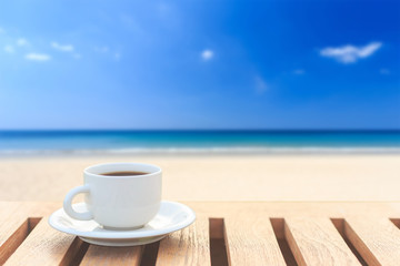 Coffee cup on wood table and view of tropical beach