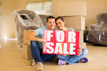 moving couple holding for sale sign