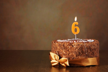 Birthday chocolate cake with burning candle as a number six on brown background