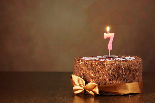 Birthday chocolate cake with burning candle as a number seven on brown background