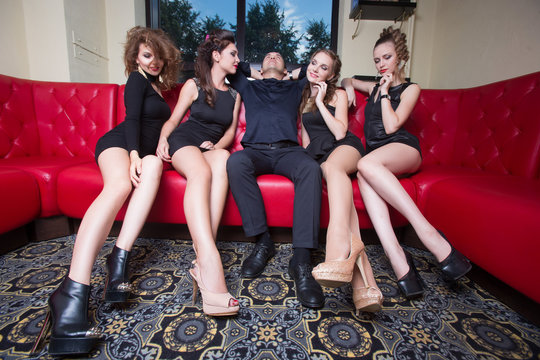 man with four girls on the sofa. in the interior