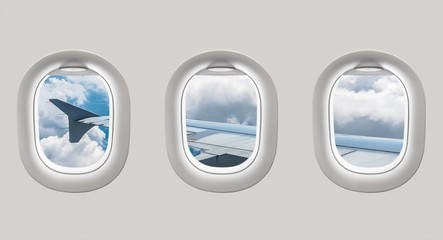Looking out the windows of a plane to the aircraft wing and clou