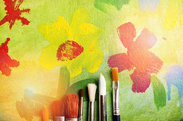 Picture of blossom flowers painted by child. Painting brushes.
