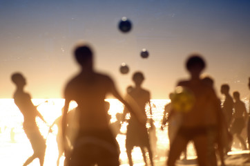 Silhouettes of Brazilians playing keepy uppy altinho futebol beach football soccer in the waves at Posto Nove Ipanema Beach Rio de Janeiro
