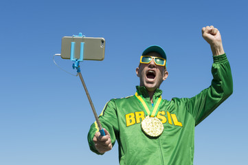 Gold medal athlete in Brazil jacket makes an excited face as he poses for a celebration picture