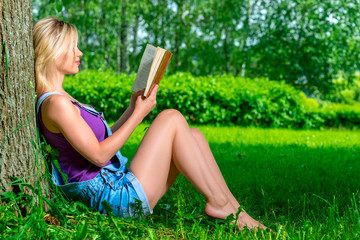 slim young girl reading a book sitting near a tree