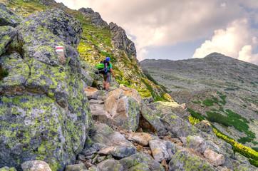Hiker on the mountain trail. A tourist in High Tatra Mountains, Slovakia.