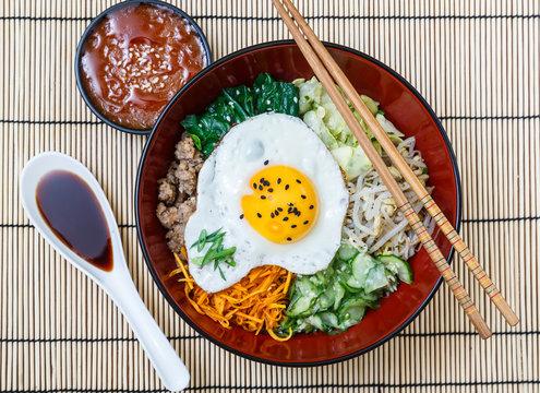bibimbap in a bowl with sauces on bamboo mat, korean dish
