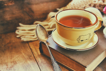 Cup of tea with old book and a warm scarf on wooden table