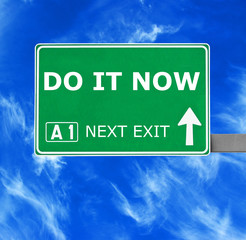 DO IT NOW road sign against clear blue sky