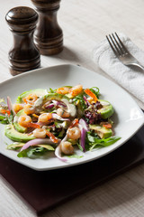 Salad with avocado and prawns on the ceramic plate with salt and pepper shaker