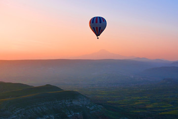Hot air balloon flying over amazing landscape at sunrise, Cappad