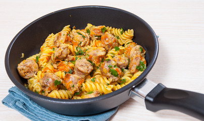 Fusilli pasta with sausage and vegetables in a frying pan
