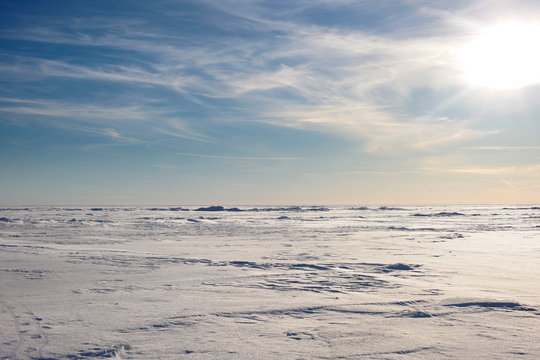 Snow desert and blue winter sky. Mountains on the horizon