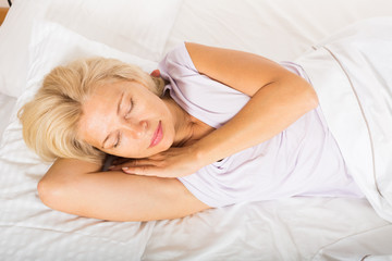 Middle-aged woman sleeping in bed