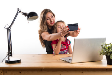 Mother and daughter working in office
