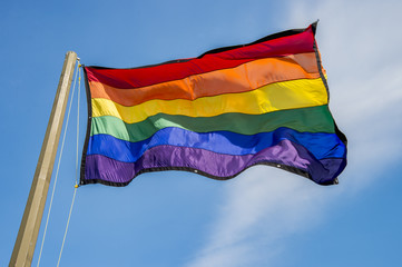 Gay rainbow flag waving over blue sky background