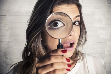 Beautiful girl using magnifying glass