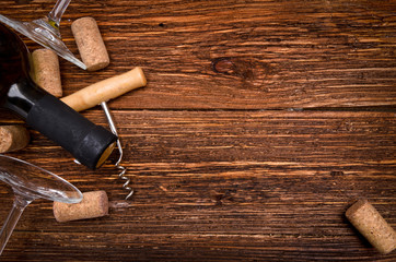 Bottle of  wine, corkscrew and corks on wooden table. Background