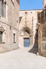 Side entrance to the Cathedral La Catedral de la Santa Creu i Santa Eulalia in the world famous Barri Gotic Barcelona. It is seat of the Archbishop. The cathedral was constructed from the 13th to 15th