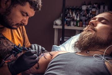 Tattooer makes tattoo in tatoo salon
