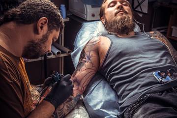 Master makes tattoo in studio