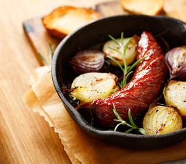 Roast sausage with onions and rosemary