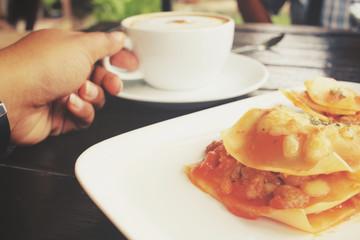 Italian lasagna with coffee cup