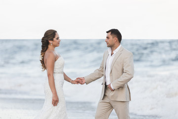 Wedding / Groom and bride walking on the beach