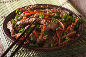 Asian cuisine: slices of beef fried with sesame and carrot close-up
