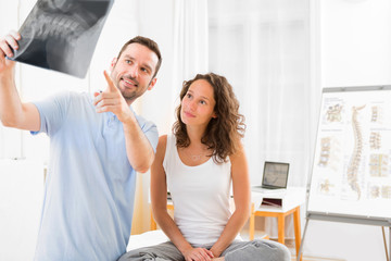 Young attractive physiotherapist analysing X-ray with patient