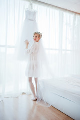 gentle bride in gown looked at her wedding dress