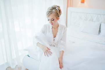gentle blonde  bride on couch with wedding dress