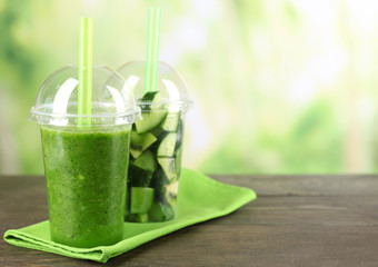 Green vegetable and fruit salad and healthy fresh drink in plastic cups on bright background. Colorful diet concept