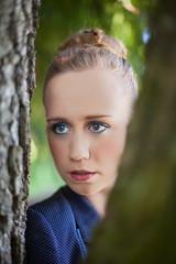 Junge Frau schaut durch Baum-Stämme