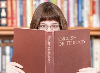 girl looks over English Dictionary and books