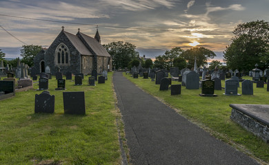 Path leading towards a UK country church at sunset