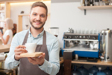 Cheerful male owner of cafeteria is serving client