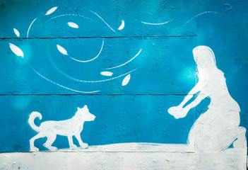 Moscow, Russia - September 27, 2015: a blue and white silhoette of a painted person on the garage wall. Woman sitting on the knees and playing with a dog.