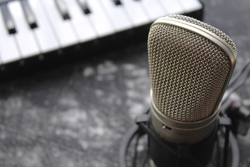 Microphone and blurred piano keys on background