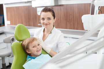 Cheerful female dentist is working with small child