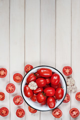 Ripe tomatoes and garlic in the white bowl
