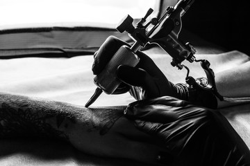 Tattooist makes tattoo on clients arm in bw