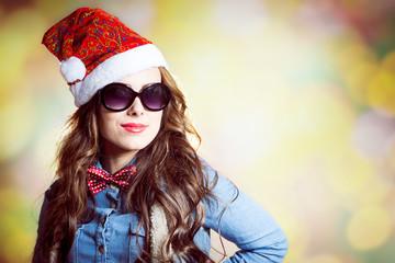 Confident girl in sunglasses wearing xmas santa hat