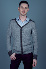 Portrait of young man with very handsome face in grey jumper and